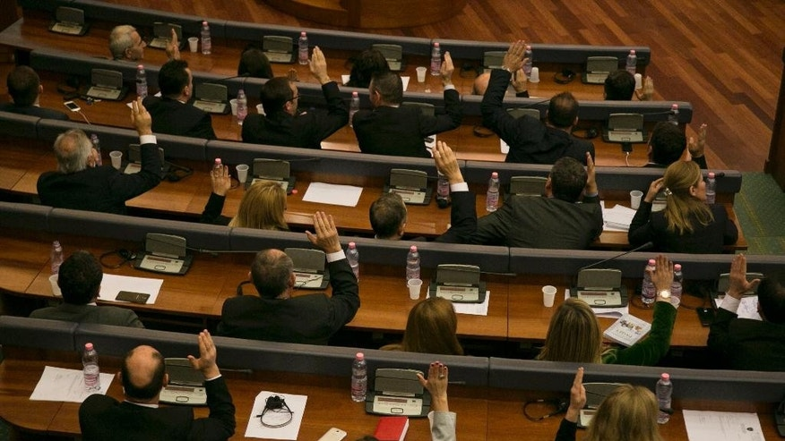 Kosovo lawmakers vote for the new government lead by newly elected Prime Minister of Kosovo Isa Mustafa at the assembly in capital Pristina, Kosovo, Tuesday, Dec. 9, 2014. The new cabinet got 73 votes in favour, while 38 lawmakers voted against and 2 abstained in the 120-seat legislature. Isa Mustafa, head of the Democratic League of Kosovo was named prime minister of a coalition government coined with former Prime Minister Hashim Thaci's Democratic Party of Kosovo. Thaci won the June 8 poll but faced an opposition bloc that refused to govern with him amid allegations of high level corruption and an international investigation into organ trafficking. (AP Photo/Visar Kryeziu)