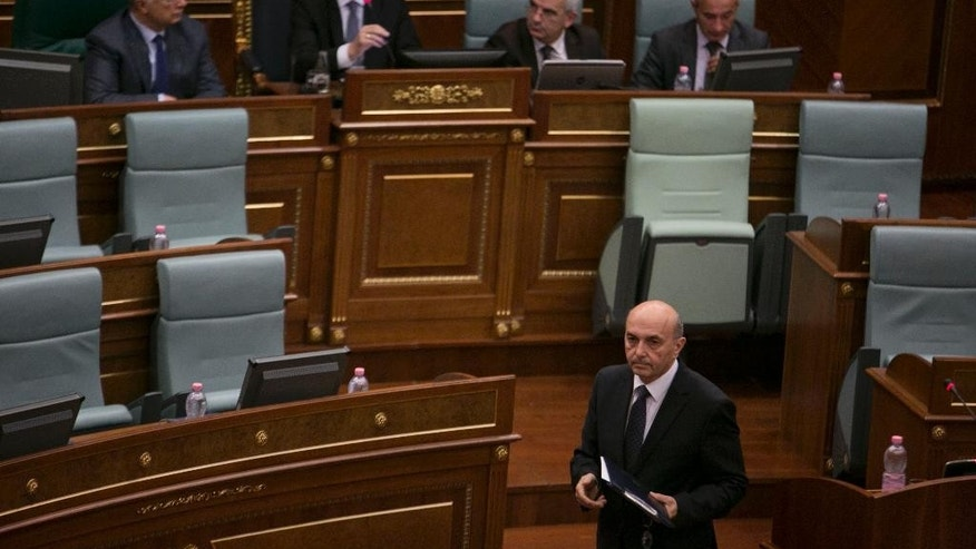 Newly elected Prime Minister of Kosovo and Leader of the Democratic League of Kosovo (LDK) Isa Mustafa, foreground, walks after being elected at the assembly in capital Pristina, Kosovo, on Tuesday, Dec. 9, 2014. The new cabinet got 73 votes in favour, while 38 lawmakers voted against and 2 abstained in the 120-seat legislature. Isa Mustafa, head of the Democratic League of Kosovo was named prime minister of a coalition government coined with former Prime Minister Hashim Thaci's Democratic Party of Kosovo. Thaci won the June 8 poll but faced an opposition bloc that refused to govern with him amid allegations of high level corruption and an international investigation into organ trafficking. (AP Photo/Visar Kryeziu)