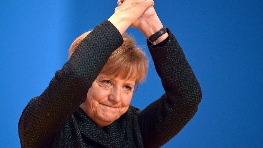 German Chancellor and chairwoman of the  Christian Democrats, CDU, Angela Merkel, thanks  delegates for  their standing ovations after her speech at the 27.  party convention in Cologne, Germany, Tuesday, Dec. 9, 2014. (AP Photo/Martin Meissner)