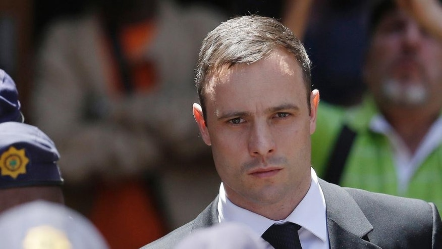 FILE - In this Friday, Oct. 17, 2014 file photo, Oscar Pistorius is escorted by police officers as he leaves the high court in Pretoria, South Africa. Judge Thokozile Masipa listened in court  Tuesday, Dec. 9, 2014, in the appeal case against Pistorius, who was acquitted of murder for killing girlfriend Reeva Steenkamp. (AP Photo/Themba Hadebe, File)