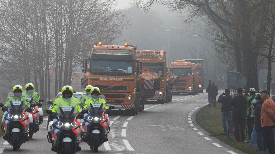 People line the road as trucks carrying parts of the wreckage of downed Malaysia Airlines flight MH17 arrive from the Ukraine at Gilze-Rijen military base, Netherlands, Tuesday, Dec. 9, 2014. The Boeing 777 plummeted from high altitude over eastern Ukraine on July 17 2014, killing all 298 passengers and crew on board. Two-thirds of the victims hailed from the Netherlands, from where the Dutch government is now leading the investigation. (AP Photo/Peter Dejong)
