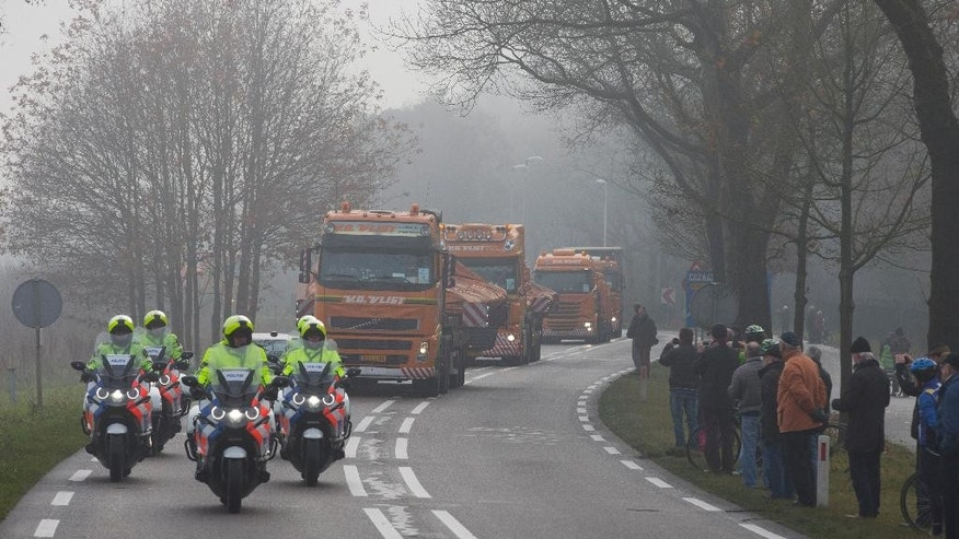 Trucks carrying the wreckage of downed Malaysia Airlines flight MH17 arrive at Gilze-Rijen military base, Netherlands, Tuesday, Dec. 9, 2014. The plane plummeted from high altitude over eastern Ukraine on July 17 2014, killing all 298 passengers and crew on board. Two-thirds of the victims hailed from the Netherlands, the reason why the Dutch government is now leading the investigation. (AP Photo/Peter Dejong)