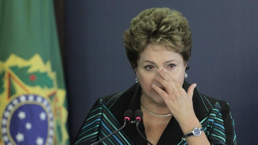 Brazil's President Dilma Rousseff cries during a speech at the launching ceremony of the National Truth Commission Report, at the Planalto Presidential Palace, in Brasilia, Brazil, Wednesday, Dec. 10, 2014. Brazil's National Truth Commission delivered a damning report on the killings, disappearances and acts of torture committed by government agents during the country's 1964-1985 military dictatorship. It called for those responsible to face prosecution. (AP Photo/Eraldo Peres)