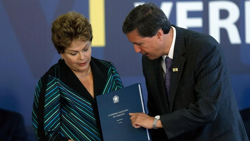 Brazil's President Dilma Rousseff, left, receives report from the President of the National Truth Commission Pedro Dallari, during the launching ceremony of the National Truth Commission Report, at the Planalto Presidential Palace, in Brasilia, Brazil, Wednesday, Dec. 10, 2014. Brazil's National Truth Commission on Wednesday delivered a damning report on the killings, disappearances and acts of torture committed by government agents during the country's 1964-1985 military dictatorship. It called for those responsible to face prosecution. (AP Photo/Eraldo Peres)