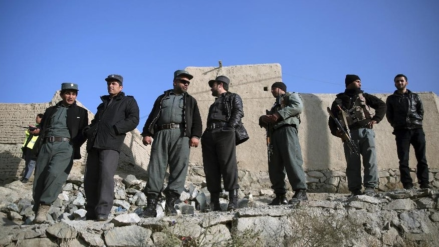 Afghan police officers look at the site of a suicide attack in Kabul, Afghanistan Thursday, Dec. 11, 2014. Police in Afghanistan's capital say a suicide bomber has killed six Afghan soldiers and wounded another 10 in the attack on a military minibus. (AP Photo/Massoud Hossaini)