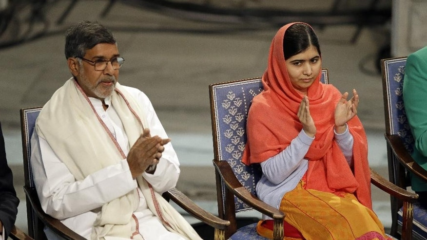 Nobel Peace Prize winners Malala Yousafzai from Pakistan, right, and Kailash Satyarthi of India take their seats during the Nobel Peace Prize award ceremony in Oslo, Norway, Wednesday, Dec. 10, 2014.  The Nobel Peace Prize is being shared between Malala Yousafzai, the 17-year-old Taliban attack survivor, and the youngest Nobel Prize winner ever, and Indian children's rights activist Kailash Satyarthi in a ceremony in Oslo on Wednesday.  (AP Photo/Matt Dunham)