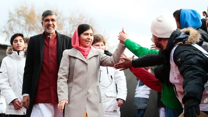 Nobel Peace Prize laureates Kailash Satyarthi, left, and Malala Yousafzai arrive at Save the Children (Redd Barna) peace prize festivities in Oslo, Wednesday, Dec. 10, 2014. (AP Photo/NTB Scanpix, Hakon Mosvold Larsen)  NORWAY OUT