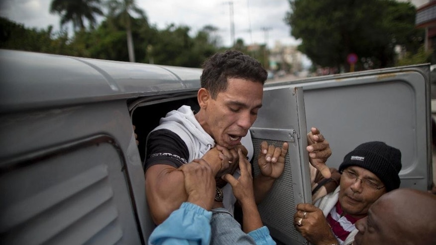 "An opposition activist is detained by Cuban security officers before the start of a march marking International Human Rights Day in Havana, Cuba, Wednesday, Dec. 10, 2014. The march was organized by the ""Damas de Blanco,"" or Women in White, a pro-democracy group of women activists. The demonstrators where picked up by the police as soon as they arrived, while hundreds of pro-government loyalists sang patriotic songs and slogans. (AP Photo/Ramon Espinosa)"