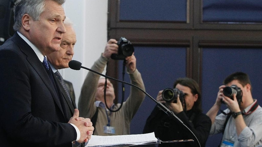 Former President Aleskander Kwasniewski, left, and former Prime Minister Leszek Miller, second left, who were in power when the CIA ran a secret prison in Poland, speak to reporters a day after the publication of a report that sheds lights on the CIA program that involved the torture of detainees, in Warsaw, Poland, Wednesday, Dec. 10, 2014. (AP Photo/Czarek Sokolowski)