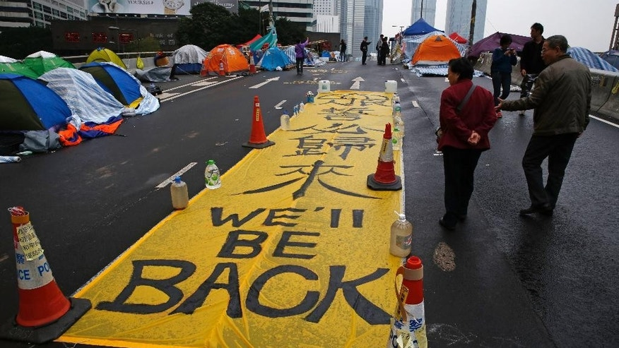 """A yellow banner reading """"We'll be back"""" is displayed by protesters at the occupied area outside government headquarters in Hong Kong Wednesday, Dec. 10, 2014. Police warned Hong Kong pro-democracy activists that they have until Thursday to leave a sprawling protest camp which has blocked traffic in the Chinese financial hub for more than two months. (AP Photo/Kin Cheung)"""