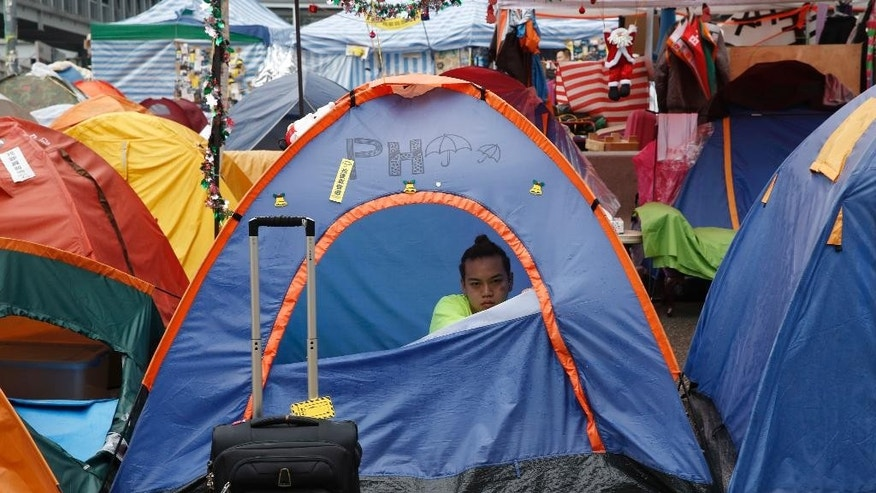 A protester sits in his tent on a main road at the occupied area outside government headquarters in Hong Kong Wednesday, Dec. 10, 2014. Police warned Hong Kong pro-democracy activists that they have until Thursday to leave a sprawling protest camp which has blocked traffic in the Chinese financial hub for more than two months. (AP Photo/Kin Cheung)