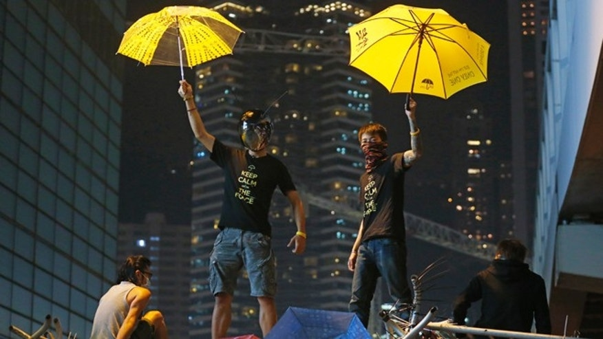 Dec. 10, 2014: Protesters pose for photographs on a barricade at the occupied area outside government headquarters in Hong Kong. (AP)