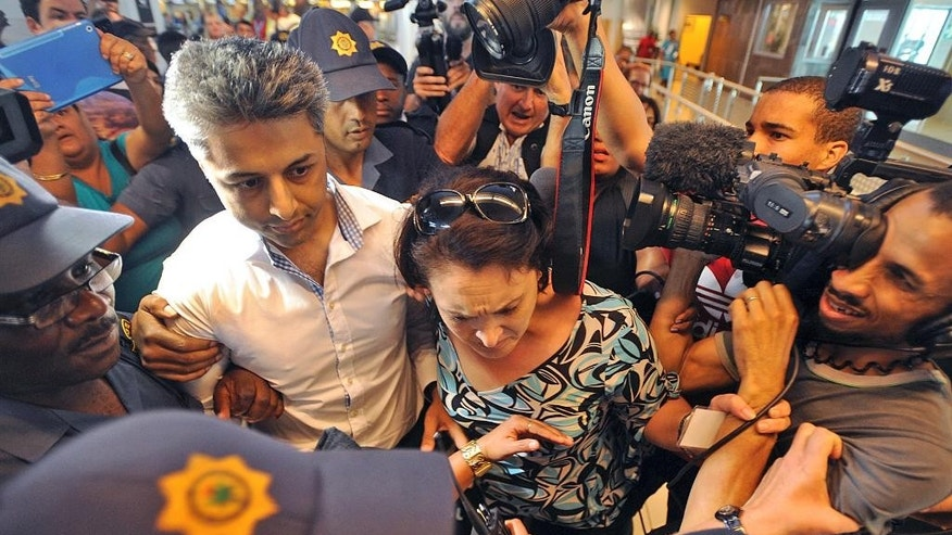 British businessman Shrien Dewani,  left, arrives at the Cape Town, South Africa airport Tuesday, Dec. 9, 2014 as he prepares to fly out of the country. On Monday Dewani  had charges, relating to the murder of his newly wedded wife, Anni Dewani, thrown out of court. (AP Photo/David Ritchie - Cape Argus)  SOUTH AFRICA OUT. NO SALES, ARCHIVES