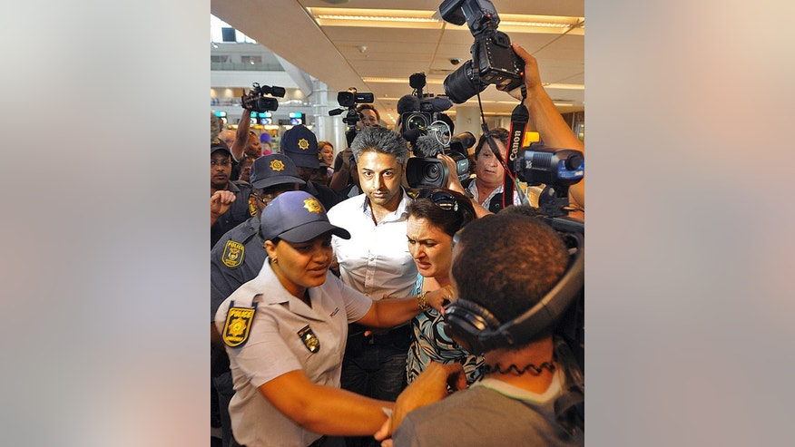 British businessman Shrien Dewani,  center, arrives at the Cape Town, South Africa airport Tuesday, Dec. 9, 2014 as he prepares to fly out of the country. On Monday Dewani  had charges, relating to the murder of his newly wedded wife, Anni Dewani, thrown out of court. (AP Photo/David Ritchie - Cape Argus)  SOUTH AFRICA OUT. NO SALES, ARCHIVES