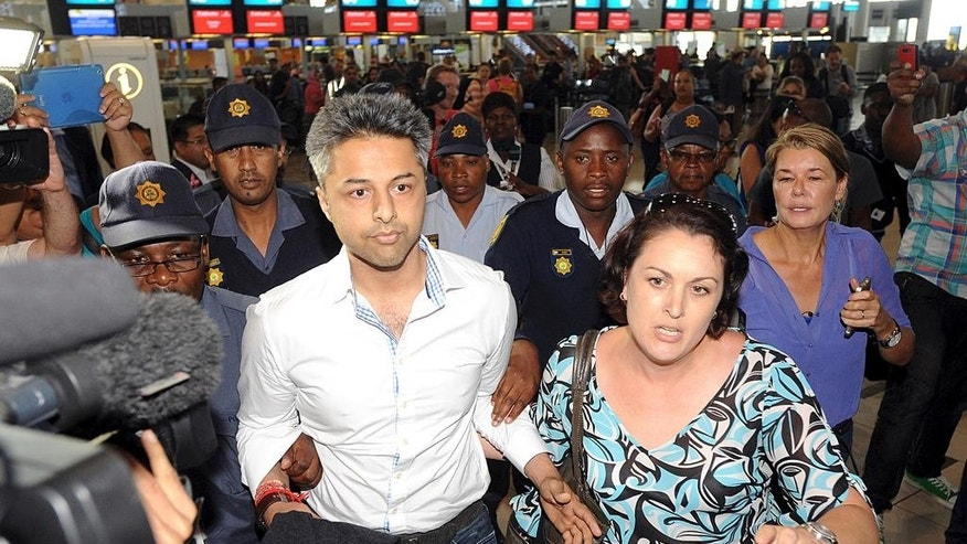 British businessman Shrien Dewani,  center left, arrives at the Cape Town, South Africa airport Tuesday, Dec. 9, 2014 as he prepares to fly out of the country. On Monday Dewani  had charges, relating to the murder of his newly wedded wife, Anni Dewani, thrown out of court. (AP Photo/David Ritchie - Cape Argus)  SOUTH AFRICA OUT. NO SALES, ARCHIVES