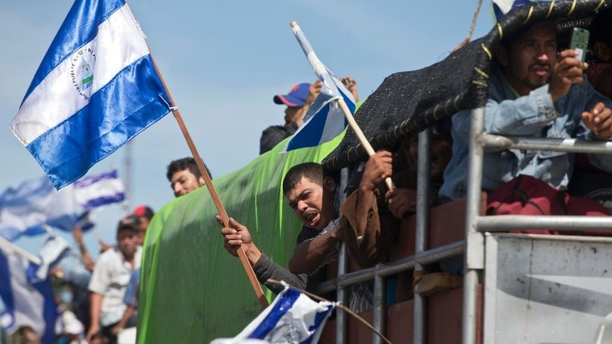 Farmers shout slogans against the construction of the Nicaraguan interoceanic canal as they arrive on trucks for a national protest march in Managua, Nicaragua, Wednesday, Dec. 10, 2014. Building of the first phase of the multi-billion dollar, 173-mile canal starts on Dec. 22. (AP Photo/Esteban Felix)
