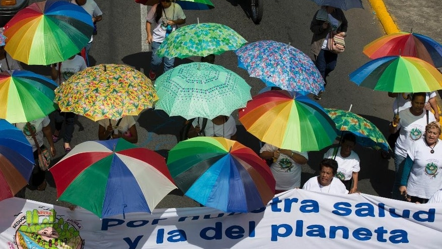 People with umbrellas to protect themselves from the sun, take part in a national march against the construction of the planned Nicaraguan interoceanic canal, Managua, Nicaragua, Wednesday, Dec. 10, 2014. Building of the first phase of the multi-billion dollar, 173-mile, canal starts on Dec, 22. (AP Photo/Esteban Felix)