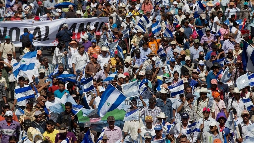People takes part in a national march against the construction of the planned Nicaraguan interoceanic canal, in Managua, Nicaragua, Wednesday, Dec. 10, 2014. Building of the first phase of the multi-billion dollar, 173-mile canal starts on Dec, 22. (AP Photo/Esteban Felix)
