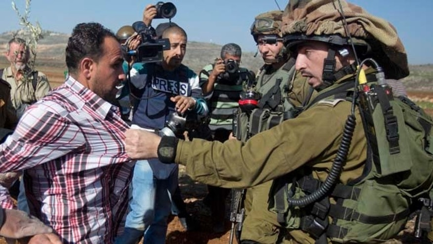 Dec. 10, 2014: An Israeli soldier pulls a Palestinian during a demonstration against Israeli settlements in the village of Turmus Aya near the West Bank city of Ramallah.
