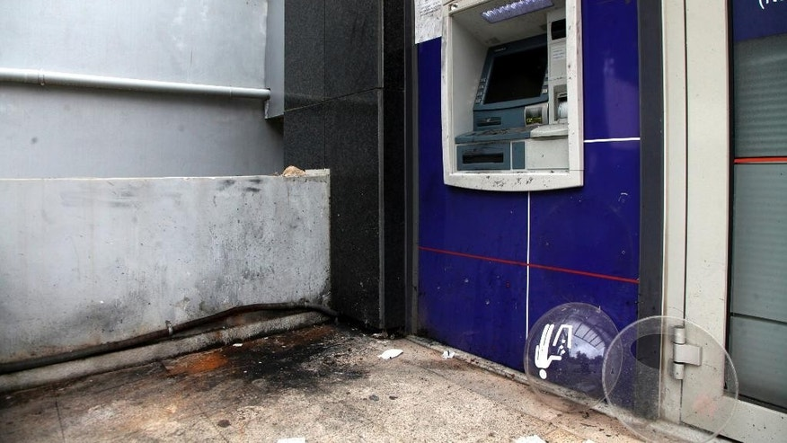 Dec. 10, 2014: The scene after a police controlled explosion is seen outside a bank in Athens. (AP)