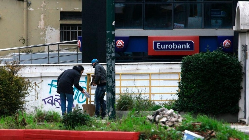 Dec. 10, 2014: Plain clothed police officers search the area outside a bank in Athens. (AP)