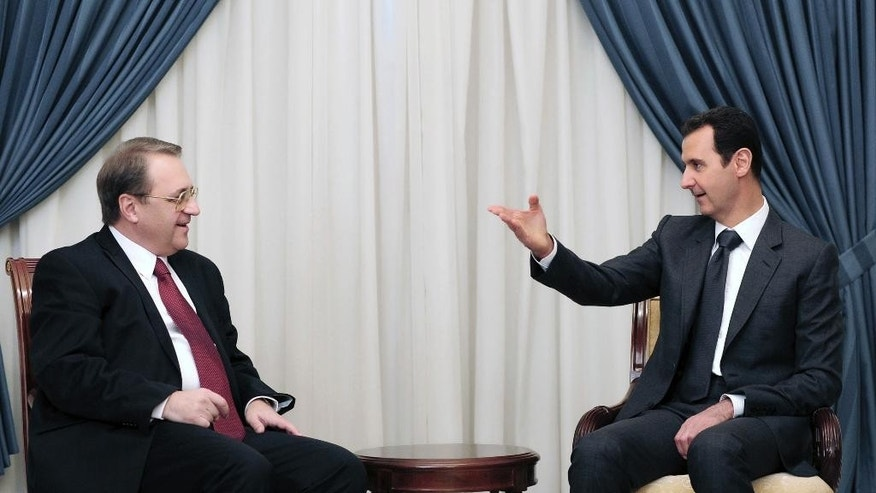 In this photo released by the Syrian official news agency SANA, Syrian President Bashar Assad, right, speaks with Russia's deputy Foreign Minister Mikhail Bogdanov in Damascus, Syria, Wednesday, Dec. 10, 2014. Bogdanov arrived in the capital Wednesday on a two-day visit for talks expected to focus on Moscow's efforts to bring all sides in Syria's seemingly intractable civil war to the negotiating table. (AP Photo/SANA)