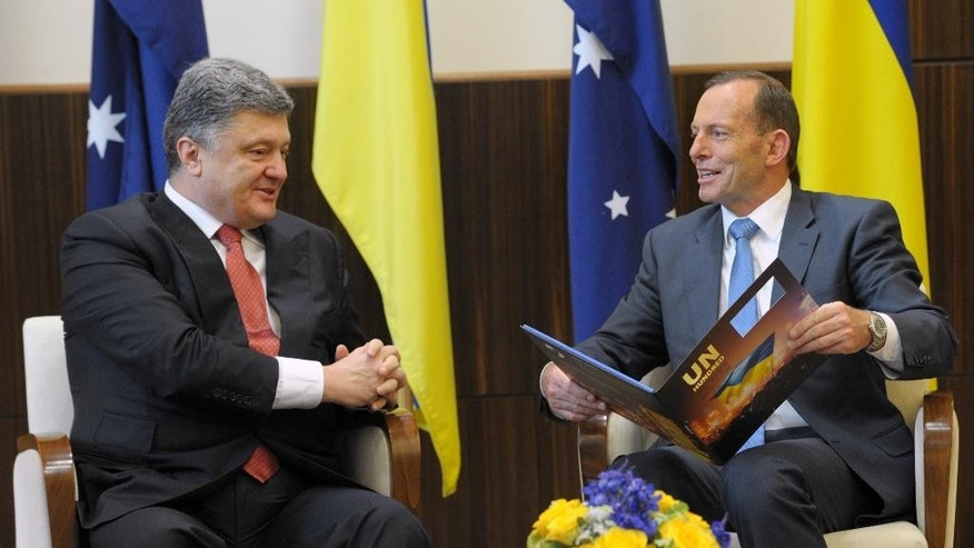 Australian Prime Minister Tony Abbott, right, holds a book given to him by Ukrainian President Petro Poroshenko as they meet at the federal government office in Melbourne, Australia, Thursday, Dec. 11, 2014. Poroshenko will travel to Canberra, Sydney and Melbourne during his two-day visit. (AP Photo/Julian Smith, Pool)