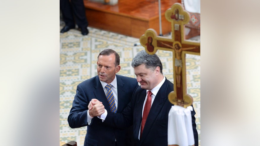 Ukraine's President Petro Poroshenko, right, and Australian Prime Minister Tony Abbott shake hands during an ecumenical church service held at Ukrainian Greek Eparchy of Saints Peter and Paul in Melbourne, Australia, Thursday, Dec. 11, 2014.  Poroshenko is on a two-day visit to Australia with talks of the downing of MH17 over Ukraine with the loss of 38 Australian citizens and residents expected to high on the agenda. (AP Photo/Mal Fairclough, Pool)