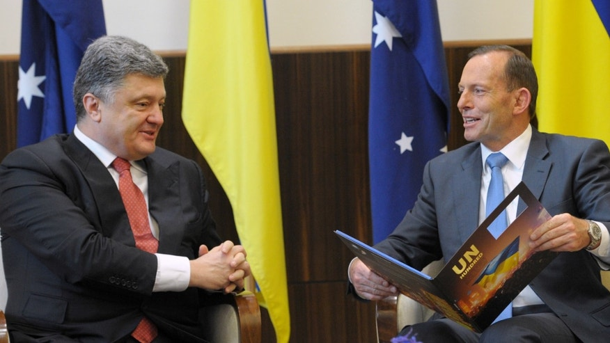 Dec. 11, 2014: Australian Prime Minister Tony Abbott, right, holds a book given to him by Ukrainian President Petro Poroshenko as they meet at the federal government office