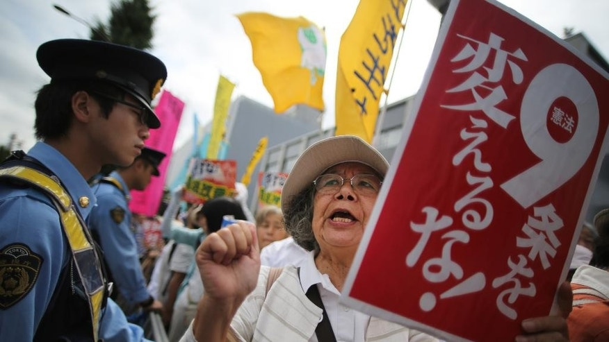 """FILE - In this Tuesday, July 1, 2014 file photo, a woman holding a placard reading """"Do not change the article 9!"""" shouts a slogan with others outside the Japanese prime minister's office in anticipation his government will reinterpret the constitution to allow Japan's military a larger international role in Tokyo. A projected landslide victory for Japan's ruling party in national elections Sunday, Dec. 14 could give Prime Minister Shinzo Abe political breathing space to push forward with his long-held nationalist agenda. While Abe has put the economy at the center of the campaign, the platform of his Liberal Democratic Party also promises to revise Japan's pacifist constitution and actively protest what it calls """"wrongful accusations"""" about the country's wartime past. (AP Photo/Eugene Hoshiko, File)"""