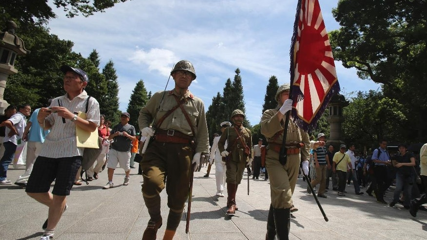 FILE - In this Friday, Aug. 15, 2014 file photo, Japanese men clad in outdated military costume march in to pay respects to the country's war dead at the Yasukuni Shrine in Tokyo as Japan marks the 69th anniversary of its surrender in World War II. A projected landslide victory for Japan's ruling party in national elections Sunday, Dec. 14 could give Prime Minister Shinzo Abe political breathing space to push forward with his long-held nationalist agenda. An immediate issue will be Abe's position on World War II history, whether he will return to the shrine that honors convicted Japanese war criminals among the war dead, and what statement he will make on the 70th anniversary of the end of World War II next August. (AP Photo/Koji Sasahara, File)