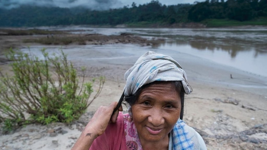 In this Nov. 17, 2014 photo, an ethnic Karen woman makes her way down to the banks of the Salween river near Tha Ta Fang, Thailand. Myanmar's government calls them signposts of modernity: a string of huge dam projects along the mighty Salween River, one of Asia's last untamed waterways, needed to meet economic goals and energy demands as the country opens its doors to the outside world. Yet to the Shan, Karen, Karenni and other ethnic minorities living in the river's basin, the six proposed hydro-power dams symbolize violence, anxiety about the future and a tool used by authorities to secure a greater grip over their lives. (AP Photo/David Longstreath)