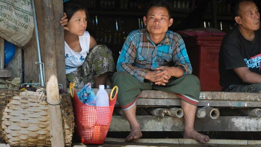 In this Nov. 16, 2014 photo, Ethnic Karen and others wait for transportation at the river port of Mae San Laep, Thailand. Myanmar's government calls them signposts of modernity: a string of huge dam projects along the mighty Salween River, one of Asia's last untamed waterways, needed to meet economic goals and energy demands as the country opens its doors to the outside world. Yet to the Shan, Karen, Karenni and other ethnic minorities living in the river's basin, the six proposed hydro-power dams symbolize violence, anxiety about the future and a tool used by authorities to secure a greater grip over their lives.  (AP Photo/David Longstreath)