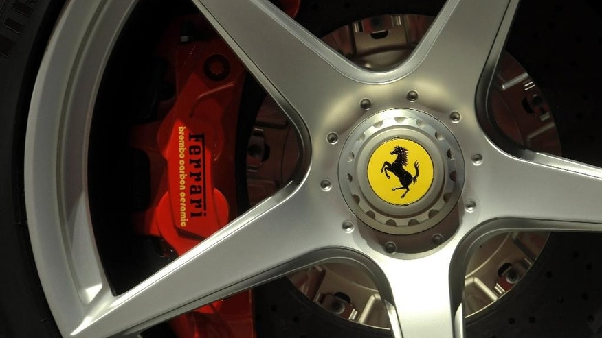 FILE - This May 8, 2013 file photo shows a Ferrari logo on a wheel at the Ferrari factory in Maranello, Italy. Ferrari's sleek sports cars and souped-up Formula 1 racing machines have made the prancing horse logo among the world's most powerful brands. Now, as the company prepares for a public listing, it wants to cash in on the cachet. (AP Photo/Marco Vasini, File)