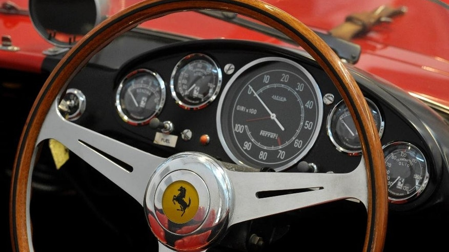 FILE - This May 8, 2013 file photo shows a Ferrari logo on a steering wheel at the Ferrari department factory in Maranello, Italy. Ferrari's sleek sports cars and souped-up Formula 1 racing machines have made the prancing horse logo among the world's most powerful brands. Now, as the company prepares for a public listing, it wants to cash in on the cachet. (AP Photo/Marco Vasini, File)