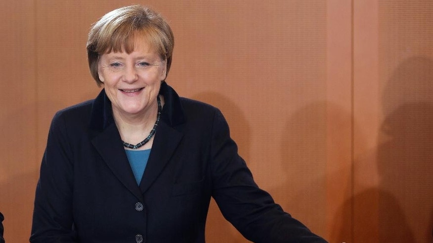 German Chancellor Angela Merkel smiles as she arrives for the weekly cabinet meeting at the chancellery in Berlin, Germany, Thursday, Dec. 11, 2014. (AP Photo/Michael Sohn)