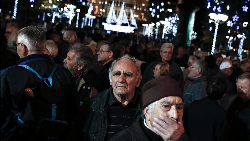 Pensioners take part in a protest outside the Finance Ministry and in front of Christmas decorations outside Greece's Parliament in central Athens on Wednesday, Dec. 10, 2014. The protesters demanded a return of benefits axed under successive austerity measures. Greece's draconian bailout program faces an uncertain future as the conservative-led government could be forced to hold a snap election early in 2015. The uncertainty has spooked investors, triggering a heaving sell off on the Athens Stock Exchange. (AP Photo/Petros Giannakouris)