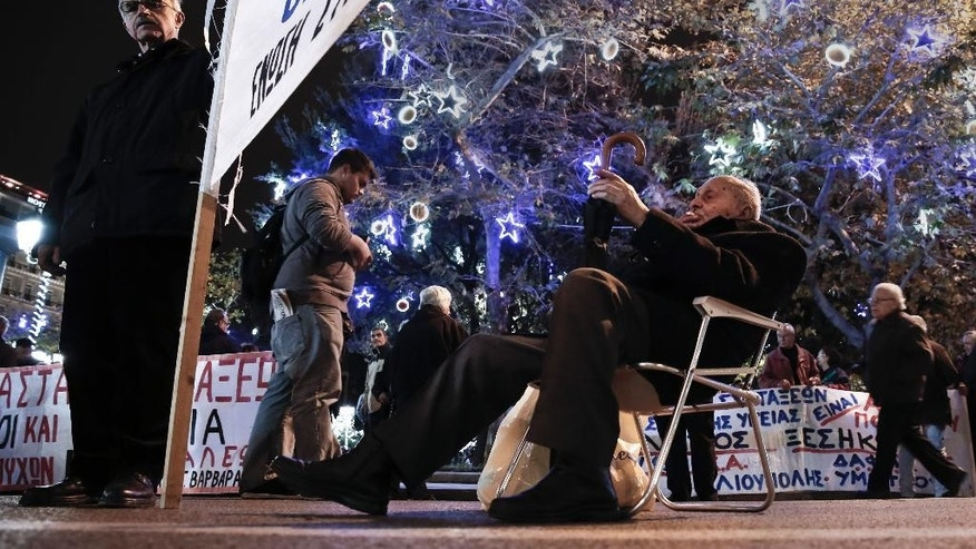 Pensioners take part in a protest outside the Finance Ministry and in front of Christmas decorations of Syntagma square in central Athens on Wednesday, Dec. 10, 2014. The protesters demanded a return of benefits axed under successive austerity measures. Greece's draconian bailout program faces an uncertain future as the conservative-led government could be forced to hold a snap election early in 2015. The uncertainty has spooked investors, triggering a heaving sell off on the Athens Stock Exchange. (AP Photo/Petros Giannakouris)
