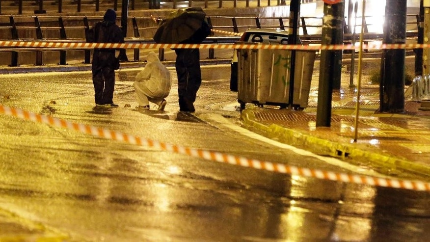Police forensic experts investigate an area near Israeli Embassy in Athens, early Friday, Dec. 12, 2014. Greek authorities are investigating a pre-dawn, drive-by gunfire attack on the Israeli embassy in Athens, which caused no injuries or damage. (AP Photo/Thanassis Stavrakis)