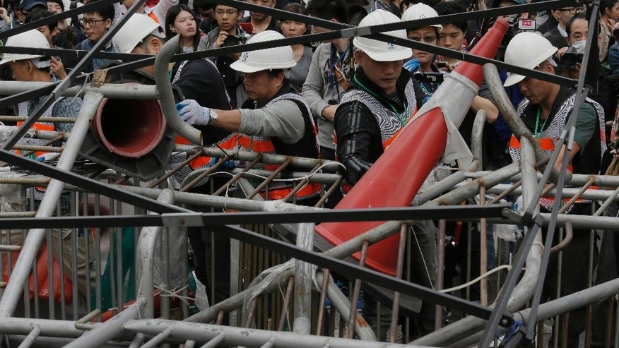 Workers clear barricades at an occupied area in Mong Kok district of Hong Kong Thursday, Dec. 11, 2014. Hong Kong authorities started clearing barricades Thursday from a pro-democracy protest camp spread across a busy highway as part of a final push to retake streets occupied by activists for two and a half months. (AP Photo/Vincent Yu)