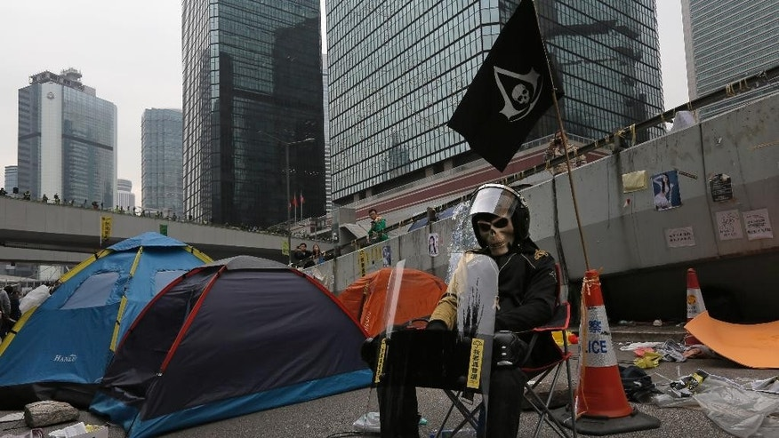 A protester sits at a main road as workers start clearing barricades at an occupied area in Mong Kok district of Hong Kong Thursday, Dec. 11, 2014. Hong Kong authorities started clearing barricades Thursday from a pro-democracy protest camp spread across a busy highway as part of a final push to retake streets occupied by activists for two and a half months. (AP Photo/Vincent Yu)