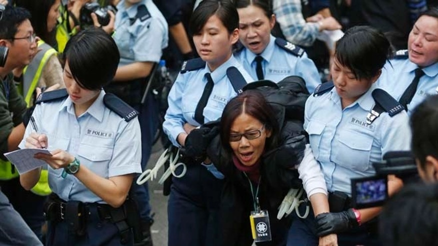 Dec. 11, 2014: Police officers take away a protester at the occupied area outside government headquarters in Hong Kong. Hong Kong authorities started clearing barricades Thursday from a pro-democracy protest camp spread across a busy highway as part of a final push to retake streets occupied by activists for two and a half months.