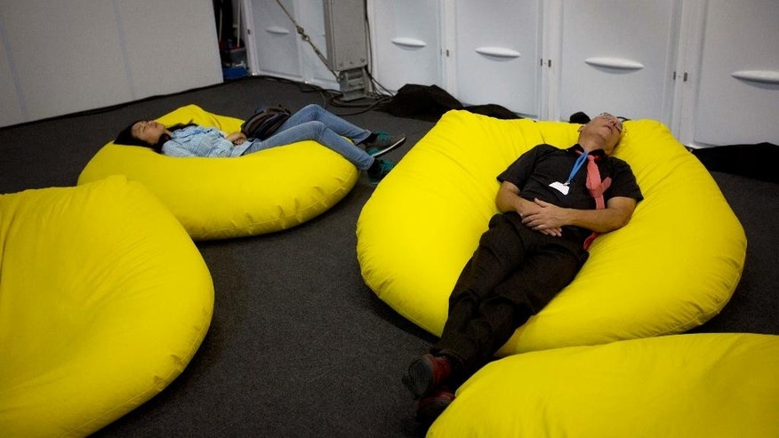 People nap during breaks at the U.N. Climate Change Conference in Lima, Peru, Thursday, Dec. 11, 2014. More than 190 countries are meeting to work on drafts for a global climate deal that is supposed to be adopted next year in Paris. (AP Photo/Rodrigo Abd)