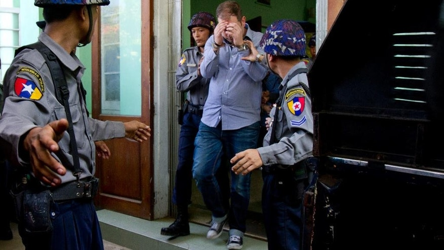 In this Thursday, Dec. 11, 2014 photo, New Zealand citizen Philip Blackwood, center, is escorted by Myanmar police officers following a court appearance in Yangon, Myanmar. Blackwood, the manager of V Gastro Bar in Yangon has been arrested for allegedly insulting Buddhism after posting an online advertisement showing a psychedelic image of Buddha wearing headphones, police said Friday. (AP Photo/Khin Maung Win)