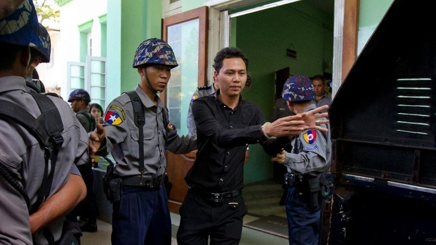 In this Dec.11, 2014 photo, Htut Ko Ko Lwin, center, an employer of V Gastro Bar, is escorted by Myanmar police officers following a court appearance in Yangon, Myanmar. The employee, a New Zealand bar manager and the bar's owner have been arrested for allegedly insulting Buddhism after posting an online advertisement showing a psychedelic image of Buddha wearing headphones. (AP Photo/Khin Maung Win)