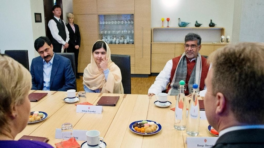 Norwegian Prime Minister, Erna Solberg, front left, and Foreign Minister, Borge Brende, front right, meet with Nobel Peace Prize Laureates Kailash Satyarthi, right, and Malala Yousafzai, centre, in the Prime Minister's office in Oslo, Thursday, Dec. 11, 2014. At left is Malala's father, Zai Uddin. (AP Photo/NTB Scanpix, Hakon Mosvold Larsen)  NORWAY OUT