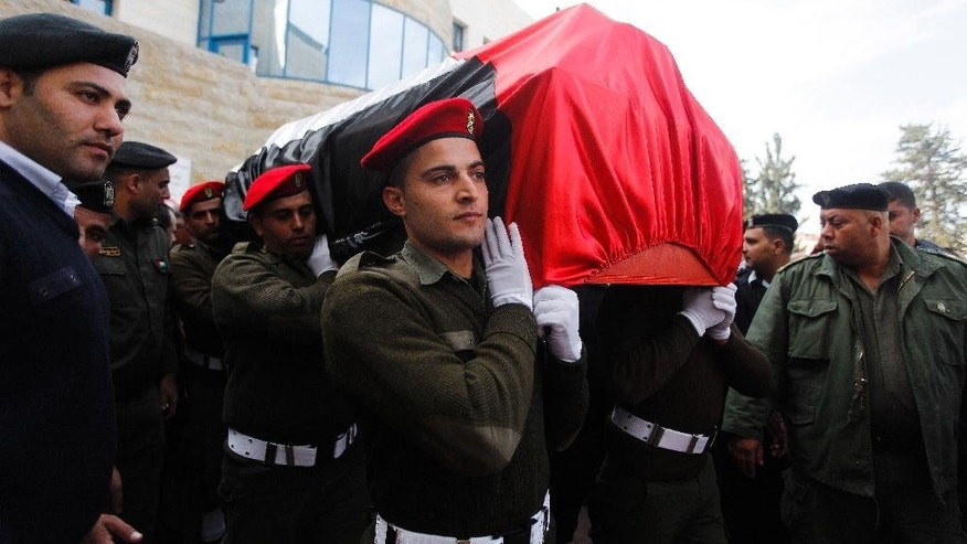 Members of the Palestinian national security forces carry the body Palestinian Cabinet member Ziad Abu Ain during his funeral in the West Bank city of Ramallah, Thursday, Dec. 11, 2014. Abu Ain died shortly after a protest in the village of Turmus Aya, near Ramallah, during which witnesses said Israeli troops fired tear gas at him and dozens of Palestinians marchers. Witnesses also said Abu Ain, was beaten by an Israeli soldier. The events began with a march to agricultural land close to an Israeli settlement, that is mostly off limits to the village's farmers, to plant olive tree saplings, participants said. (AP Photo/Majdi Mohammed)