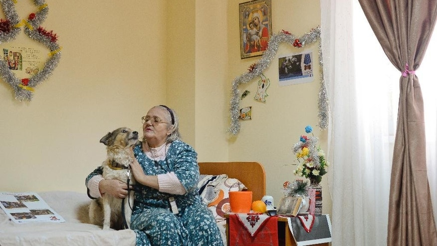 "FILE - In this Wednesday, Dec. 10, 2014 file photo, Elena Calugaru, 60, pets Tibi, a 11 year old stray dog, in Bucharest, Romania. Elena Calugaru, 60, calls Tibi ""my boy, my love!"" and her eyes well up with tears as she cuddles him. (AP Photo/Octav Ganea, Mediafax, File) ROMANIA OUT"