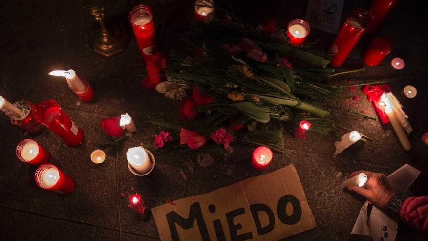 "Protestors light candles placed around a sign reading ""Fear"" as they act out a mock funeral during a pro-civil rights demonstration in the main square of Madrid, Spain, Wednesday, Dec. 10, 2014. Demonstrators march to protest against a wave of repressive laws and reforms by the conservative Popular Party government, that include draft legislation that will set heavy fines for offences such as causing disturbances outside parliament, burning the national flag, insulting the state or taking part in unauthorised or prohibited protests at strategic installations. The law will vote it on in the Parliament Thursday. (AP Photo/Andres Kudacki)"