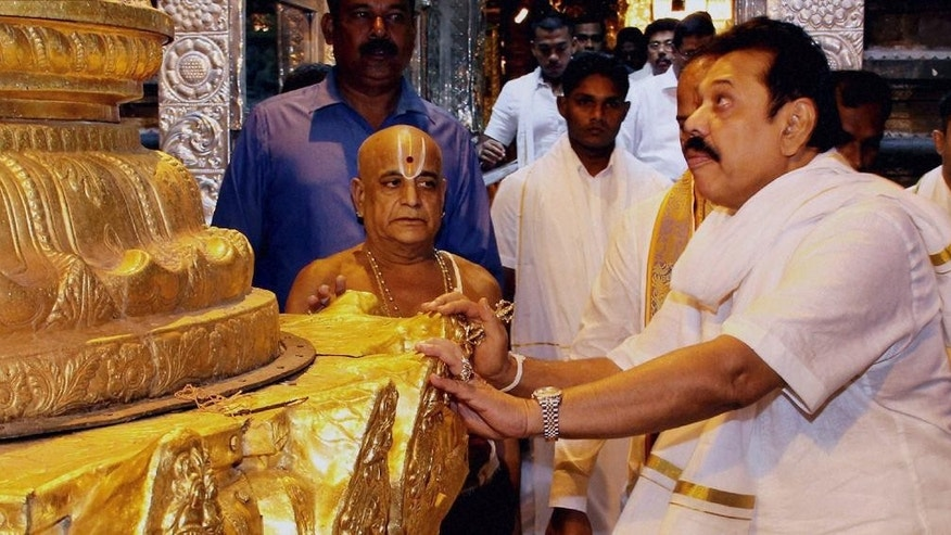 In this Wednesday, Dec.10, 2014 photo, Sri Lankan President Mahinda Rajapaksa, right, offers prayers at the Tirumala Venkateswara Hindu Temple in Tirupati, Andhra Pradesh state, India.(AP Photo/Press Trust of India) INDIA OUT